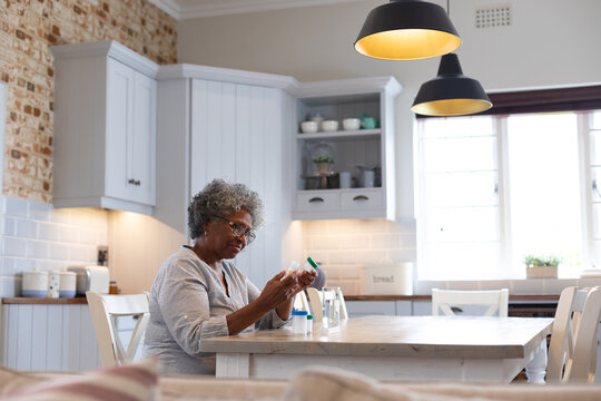Thoughtful african american senior woman holding empty medication containers at home