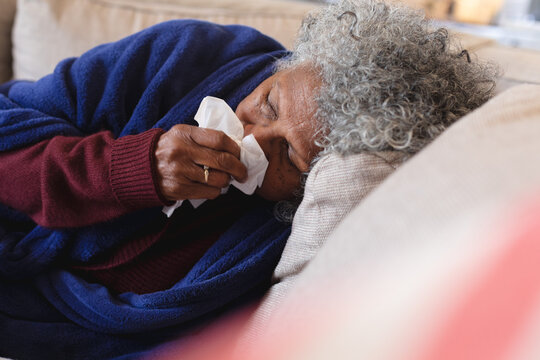 Sick african american senior woman lying on the couch