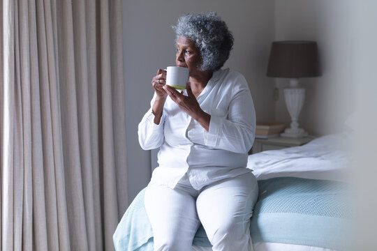 Thoughtful african american senior woman drinking coffee while sitting on bed at home
