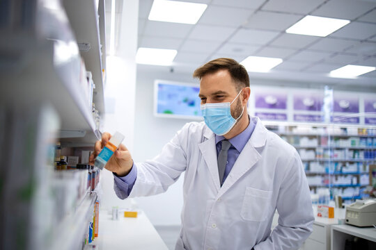 Pharmacist wearing face mask and white coat choosing appropriate vitamins in pharmacy store to sell to the customer during corona virus pandemic. Healthcare and medicine.