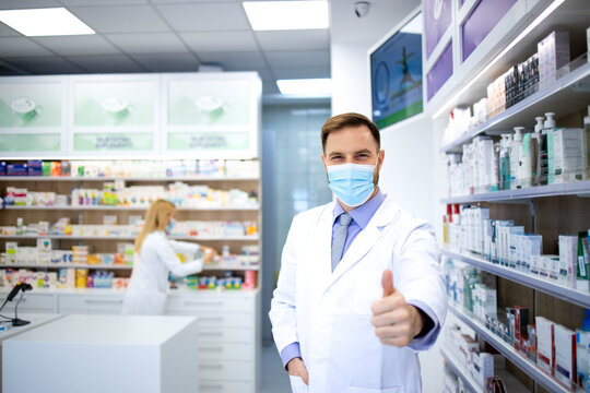 Portrait of pharmacist wearing face mask and white coat showing thumbs up in pharmacy store during corona virus pandemic.