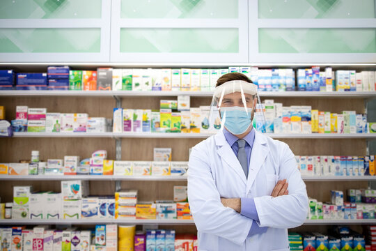 Portrait of pharmacist wearing face shield and white coat standing in pharmacy store during corona virus pandemic.