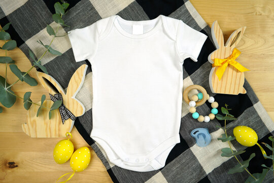 Easter farmhouse theme baby apparel top view flatlay. Mock up. Bodysuit, romper onesie mock up with negative copy space for your text or design here.