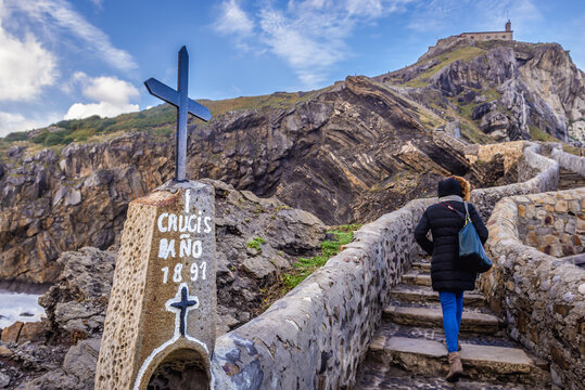 Tourist on a stairs to hermitage on Gaztelugatxe island on the Atlantic shore, Spain
