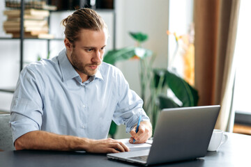 Obraz Concentrated caucasian guy freelancer or student uses laptop, distant learners or work. Focused attractive modern man in stylish casual wear sits at the desk in a creative or home office, browsing - fototapety do salonu