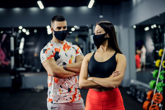 Muscular couple standing in gym with arms crossed with face masks during corona virus. Prevention from corona virus, fitness, healthy life