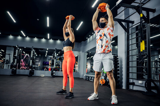 Sporty couple in shape with face masks standing in gym and lifting weights. Healthy lifestyle, sport during corona, bodybuilding