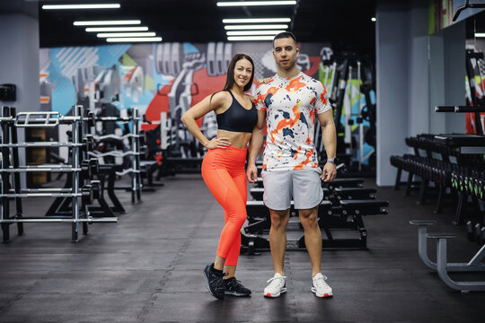 Fit sporty couple standing in gym and posing. Bodybuilding, healthy habits, indoor fitness