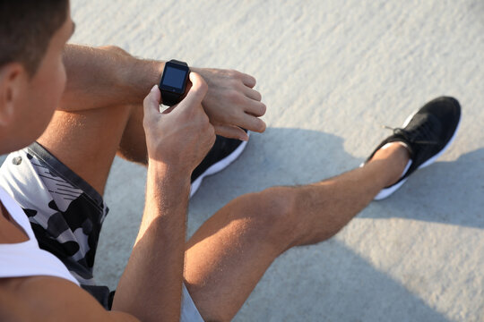 Man checking fitness tracker after training outdoors, closeup