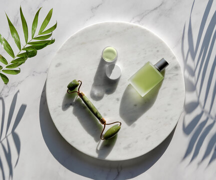 Jade face roller and herbal infusion for facial massage therapy. Flat lay on round marble podium on stone table with exotic palm leaf. Simple arrangement, sunlight, long shadows