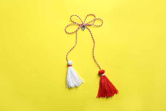Traditional martisor on yellow background, top view. Beginning of spring celebration