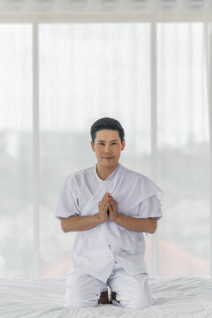 Religious Asian buddhist man in white cloth praying and chanting at home