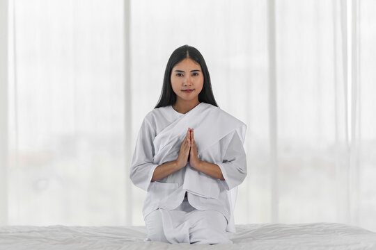 Religious Asian buddhist woman in white cloth praying and chanting