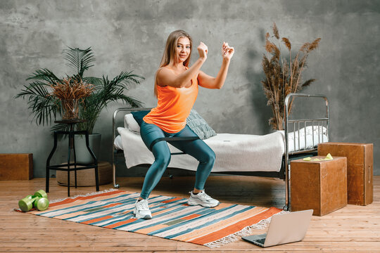 The beauty woman goes in for sports at home. Cheerful sporty woman with  blond hair  doing a squat with sport fitness rubber bands     and watches  in laptop, shootting  blog  in the bedroom