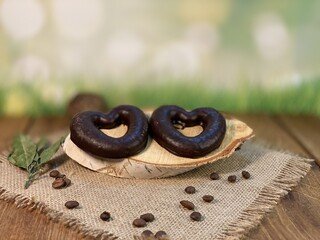 Oak table with visible rings of chocolate gingerbread in the shape of a heart. Coffee beans are...