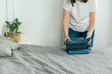 Fototapeta Woman folding clothes jeans. Wardrobe analysis, spring update, decluttering concept. Mock up obraz