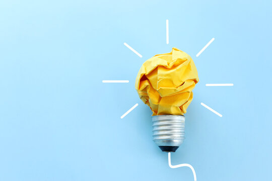 Education concept image. Creative idea and innovation. Crumpled paper as light bulb metaphor over blue background