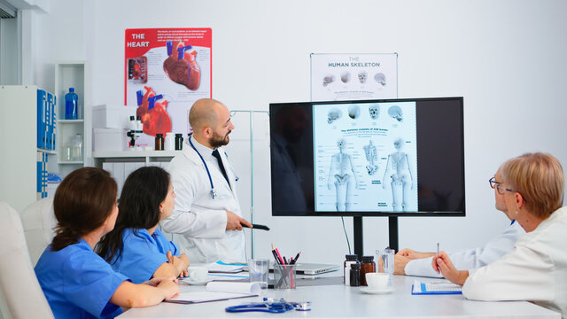 Experienced man doctor analysing human skeleton image together with cvalified colleagues in meeting room, pointing on monitor. Doctors discussing diagnosis about treatment of patients