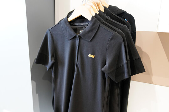BMW Motorsport M logo and brand sign on polo shirt in car dealership shop