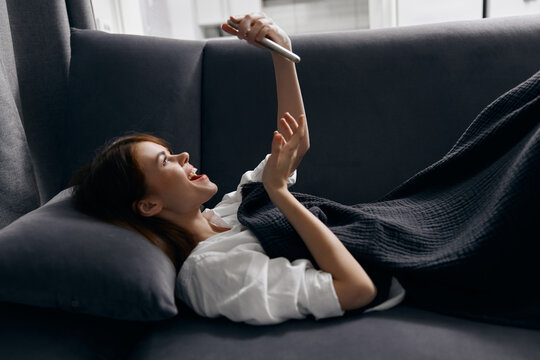 a pretty woman with a phone in her hands lies on a sofa in a room side view