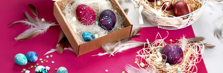 Painted Easter eggs in cardboard box and basket
