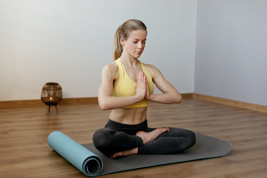 A young woman with her eyes closed meditates in the lotus position on a yoga mat. Yoga, meditation, lifestyle