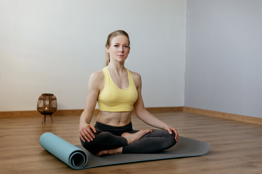 A blonde girl is resting after a fitness class and meditating. The concept of sports and a healthy lifestyle. Yoga, meditation