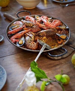 Plate with traditional tasty paella on table