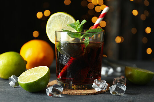 Glass of Cuba Libre on gray textured table against blurred lights