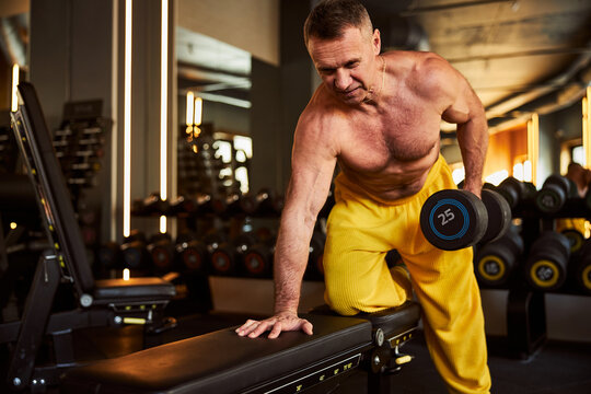 Strong man doing set of dumbbell exercises at local gym