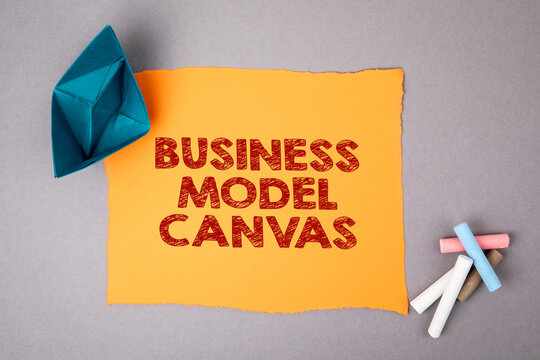 Business Model Canvas. Paper ship and sheet on a gray background