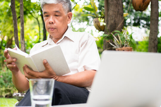 senior old man reading a book in the park and drinking water. Concept of retirement lifestyle and hobby.