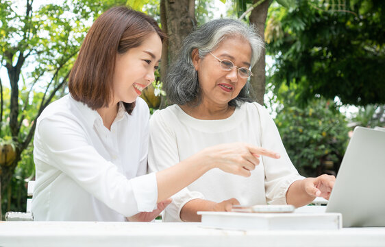 Asian daughter teaching old elderly woman use online Social media in computer laptop after retirement. Concept of Learning technology and adaptation of the elderly