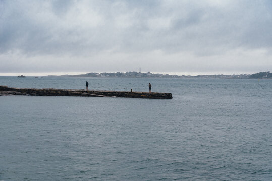 Back view of two adults standing on pier facing to the calm sea against the Island of Batz, freedom concept. Roscoff, Brittany