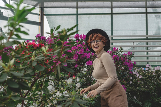 A beautiful plus size girl in a hat laughs among the green plants of the greenhouse. Cottagecore style