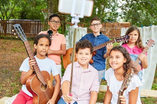 Children as a music band take selfie at summer camp
