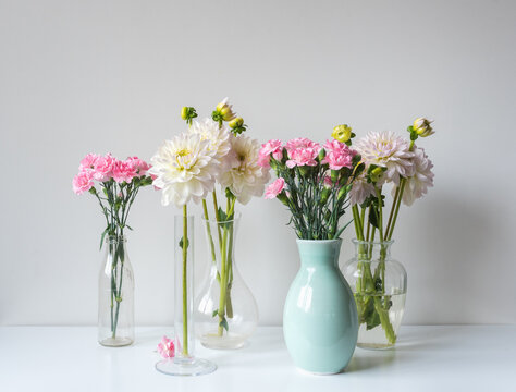 Close up of pink carnations and white dahlia flowers in glass and ceramic vases on white shelf against wall (selective focus)