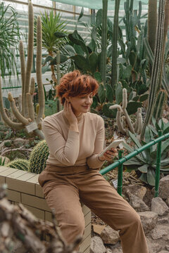 A beautiful plus size girl uses her smartphone sitting among the green plants of the greenhouse.