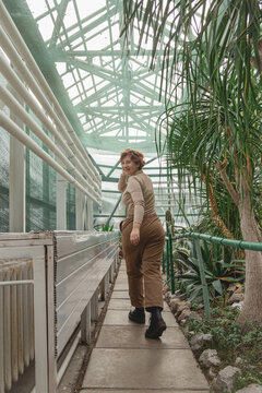 A beautiful plus size girl runs across greenhouse among the green plants. Cottagecore style. Self love concept