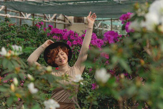 A beautiful plus size girl in a hat enjoying standing among the green plants of the greenhouse. Cottagecore style