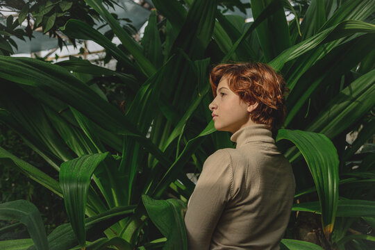 A beautiful plus size girl with red hair among the lush green branches of tropical plants. Botanical and cottage style close to nature.
