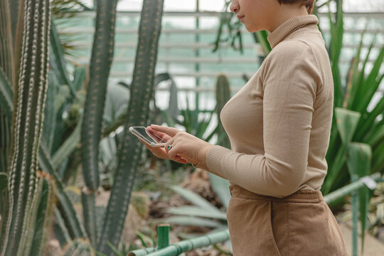 A beautiful plus size girl uses smartphone standing among the green plants of the greenhouse.