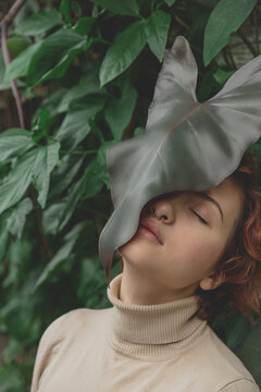 A beautiful plus size girl with red hair among the lush green branches of tropical plants. Botanical and cottage style close to nature. Faceless photo