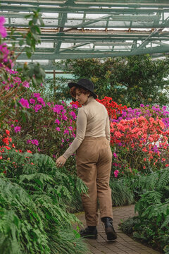 A beautiful plus size girl in a hat walking among the green plants of the greenhouse. Cottagecore style