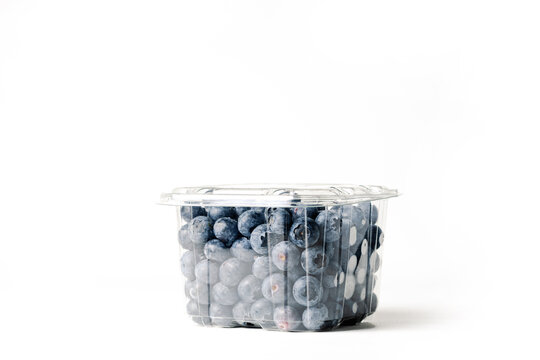 transparent jar of blueberries, on white background, with closed lid, side view