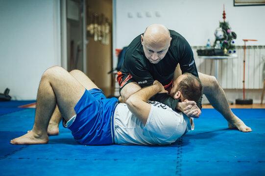 BJJ Brazilian jiu-jitsu ground fight headlock training. Neck and head lock submission control technique