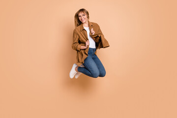 Wall Mural - Full body photo of charming energetic happy woman jump up air wear glasses isolated on beige color background