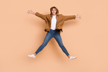 Wall Mural - Full length photo of positive funky lady jump up star shape good mood isolated on pastel beige color background