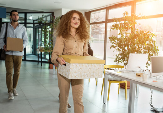 Young business people of mixed-races with boxes come back to office. Colleagues going to work in modern workspace, teamwork together. 4k Slow motion video.