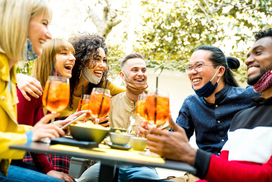 Multiracial friends wearing face masks drinking cocktails at bar restaurant - New normal friendship concept with young people enjoying meal in backyard party - Focus on guy in the middle